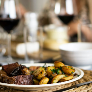 A chef-prepared dinner, plated next to wine glasses filled with red wine