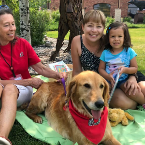 A young child and her mom sit with a therapy doc and her handler, part of the Read to a Dog program on the Library front plaza.