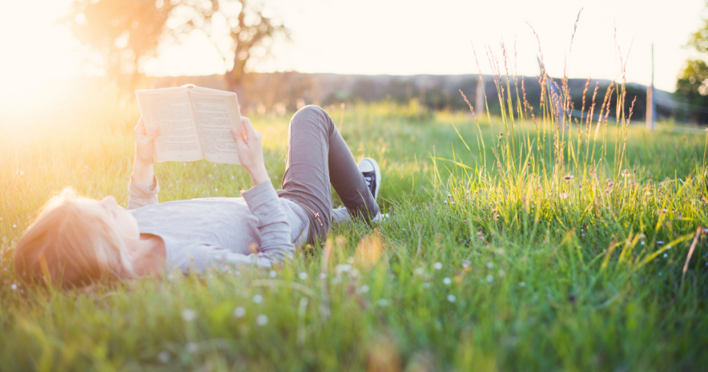 Child lying in the grass, reading
